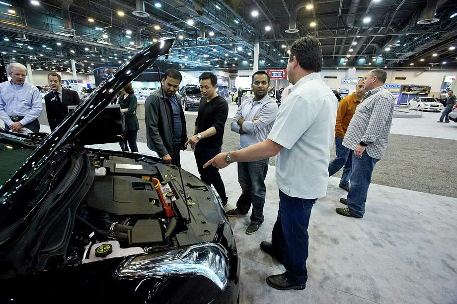 Hung Dang, in black pointing, and friends  look at the engine of  the fully electric Cadillac ELR at the Houston Auto show held at Reliant Center in Houston, Texas. The car lists for $75,000. Photo: Thomas B. Shea, Houston Chroncile / © 2013 Thomas B. Shea
