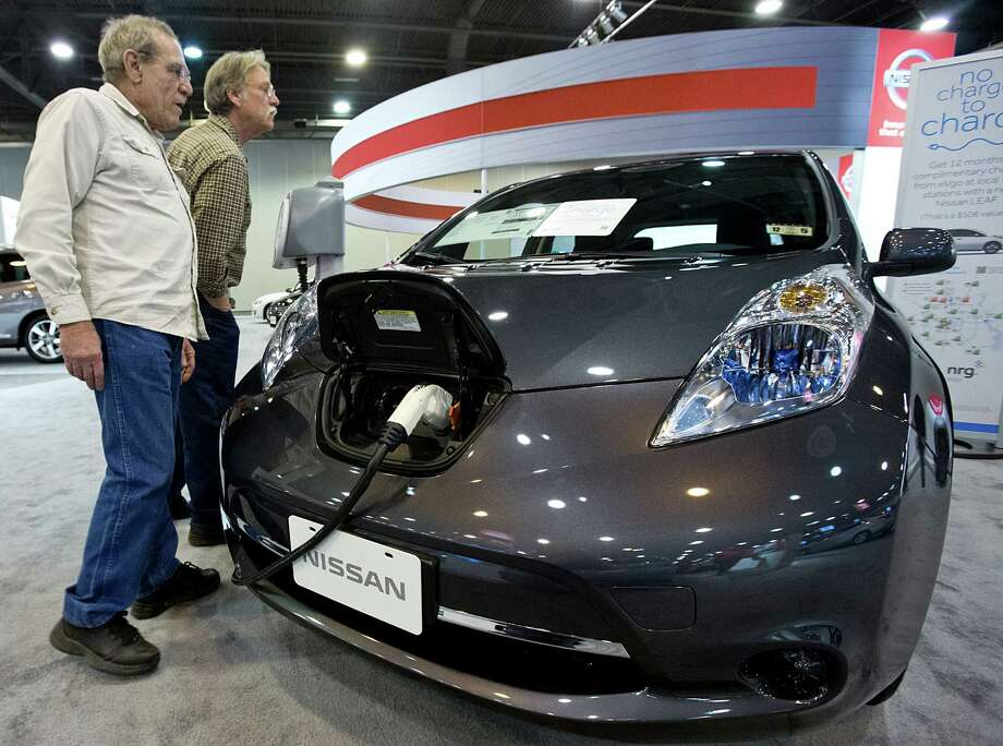 Car show attendees look at the Nissan Leaf at the Houston Auto Show held at Reliant Center. Photo: Thomas B. Shea, Houston Chroncile / © 2013 Thomas B. Shea
