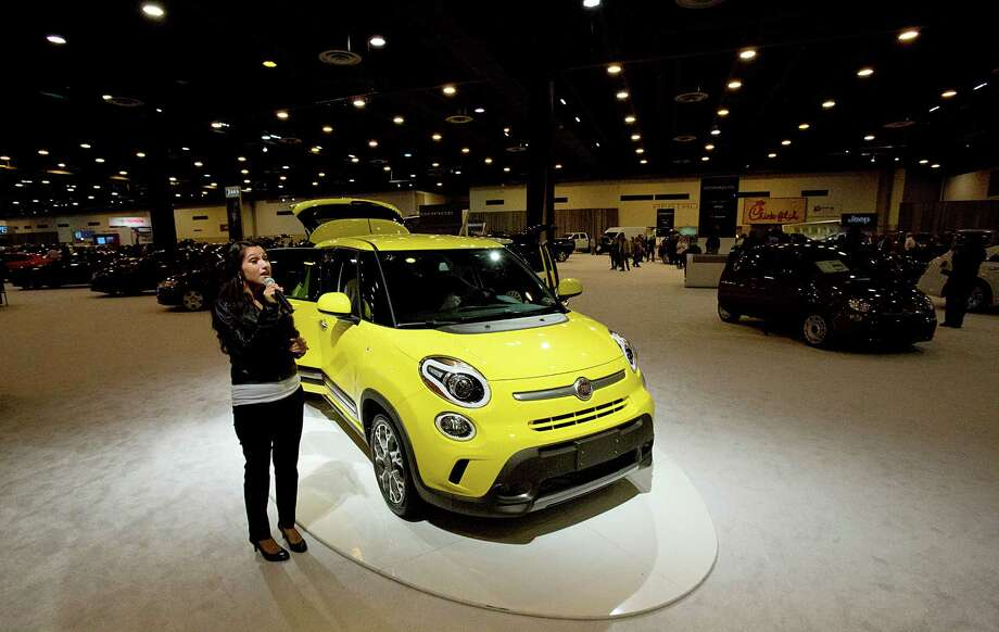 A spokesmodel talks about the 2014 Fiat 500 L at the Houston Auto Show. The car is listed for $19,900 and averages 33 miles per gallon highway. Photo: Thomas B. Shea, Houston Chroncile / © 2013 Thomas B. Shea