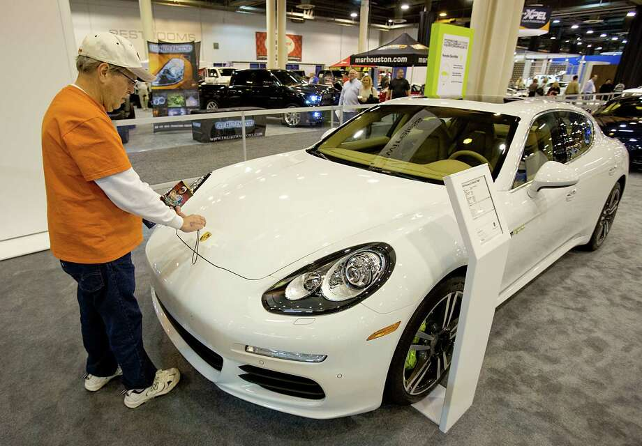 Paul Moore, from Houston, takes a photo of the Porche emblem on the Porsche 2014 Panamera S-E Hybrid at the Houston Auto Show. Photo: Thomas B. Shea, Houston Chroncile / © 2013 Thomas B. Shea