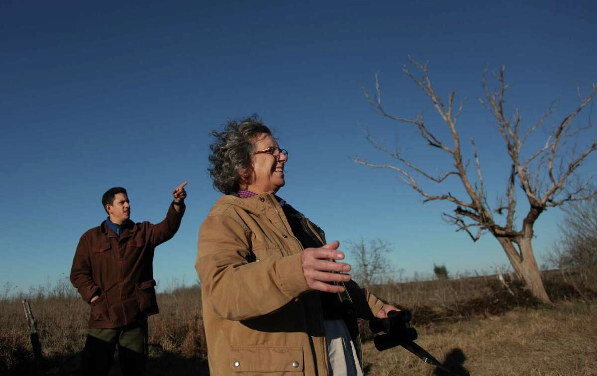 Jaime González and Mary Anne Piacentini, Katy Prairie Conservancy executive director, spot birds in the area where a proposed highway might be built on Jan. 15, 2014.