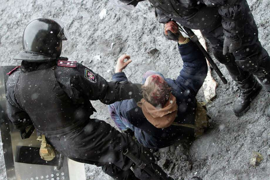 Ukrainian riot policemen detain a protester following clashes in central Kiev on January 22, 2014. Five activists were killed and 300 wounded in the Ukrainian capital Kiev in a day of intense clashes with security forces, the medical centre of the protest movement said. AFP PHOTO/ ANATOLII BOIKOANATOLII BOIKO/AFP/Getty Images Photo: ANATOLII BOIKO / AFP