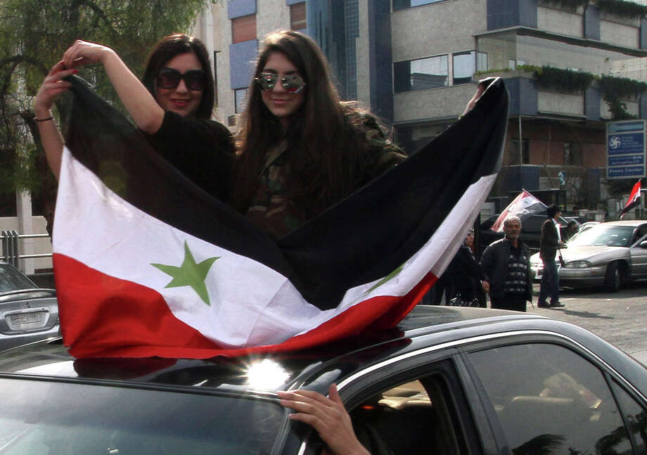 "Syrian women hold their national flag as they sit on the roof of a car on January 22, 2014 in the capital Damascus. World powers urged Syria's warring sides to seize a ""historic"" opportunity as they gathered in Switzerland for a peace conference that kicked off with bitter exchanges. AFP PHOTO / STR-/AFP/Getty Images Photo: - / AFP"