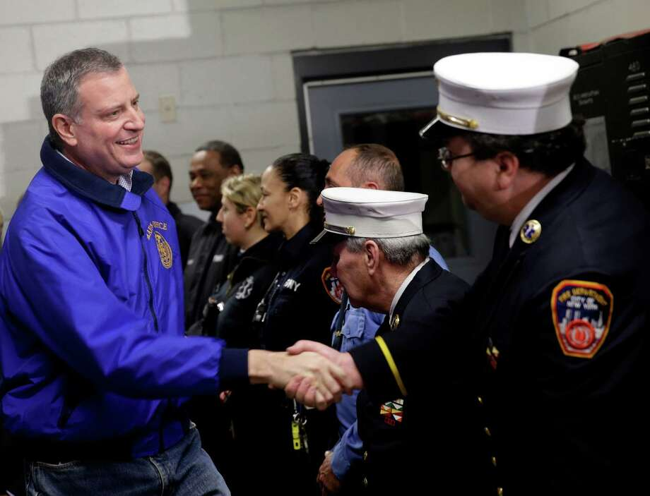 "New York City Mayor Bill de Blasio, left, greets emergency personnel before a news conference about snow removal in the Brooklyn borough of New York, Wednesday, Jan. 22, 2014.  De Blasio says ""no one was treated differently"" when it comes to snow cleanup. De Blasio said Wednesday in response to some residents' complaints that New York City has a ""five-borough approach"" to everything it does. (AP Photo/Seth Wenig) ORG XMIT: NYSW108 Photo: Seth Wenig / AP"