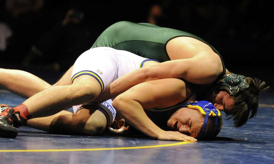 Newtown's Tom Long, bottom, wrestles New Milford's Thomas McIlveen in the 220 pound match during New Milford's 36-29 win over Newtown at Newtown High School in Newtown, Conn. on Wednesday, Jan. 22, 2014. Photo: Tyler Sizemore / The News-Times