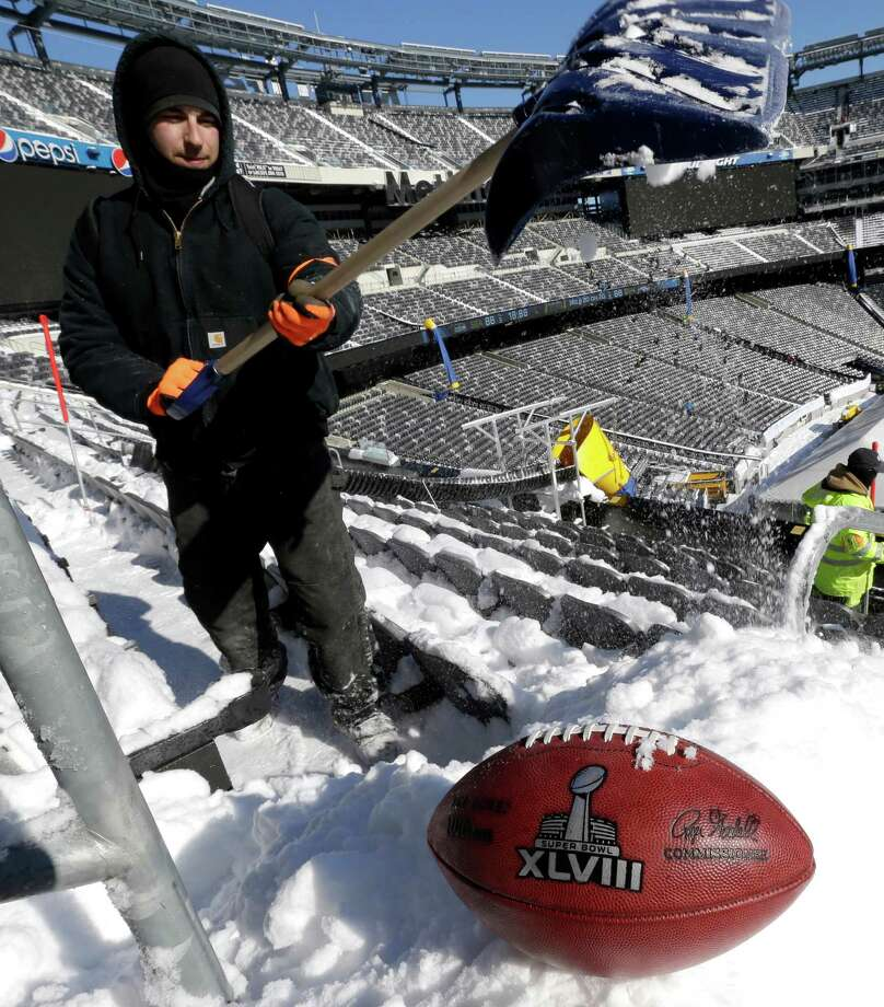 A football with the Super Bowl XLVIII logo is set on a mound of snow as an for an NFL photographer to make photos of it as workers shovel snow off the seating area at MetLife Stadium as crews removed snow ahead of Super Bowl XLVIII following a snow storm, Wednesday, Jan. 22, 2014, in East Rutherford, N.J. Super Bowl XLVIII, which will be played between the Denver Broncos and the Seattle Seahawks on Feb. 2, will be the first NFL title game held outdoors in a city where it snows. (AP Photo/Julio Cortez) ORG XMIT: NJJC119 Photo: Julio Cortez / AP