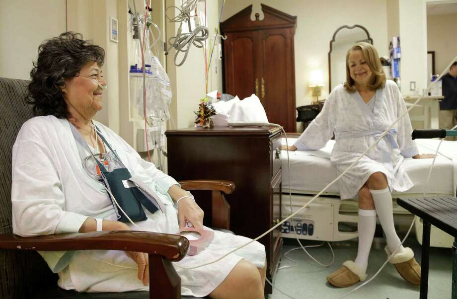 In this Jan. 14, 2014 photo, Irma Myers-Santana, left, and her sister Anna Williamson visit in Williamson's hospital room in Houston. Earlier this month the sisters ended up in the same operating room, each getting one lung from the same donor. Photo: Pat Sullivan, AP / AP