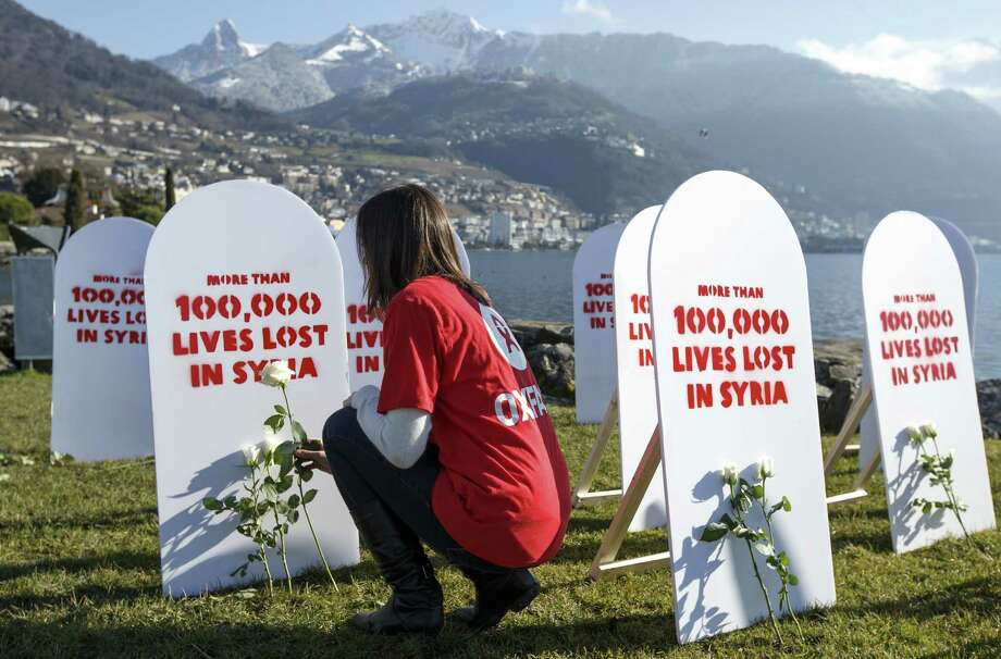 A member of the Oxford Committee for Famine Relief, or Oxfam, puts a white rose on symbolic gravestones on the opening day of the peace talks on Syria in Montreux, Switzerland. Photo: Salvatore Di Nolfi / Associated Press / KEYSTONE