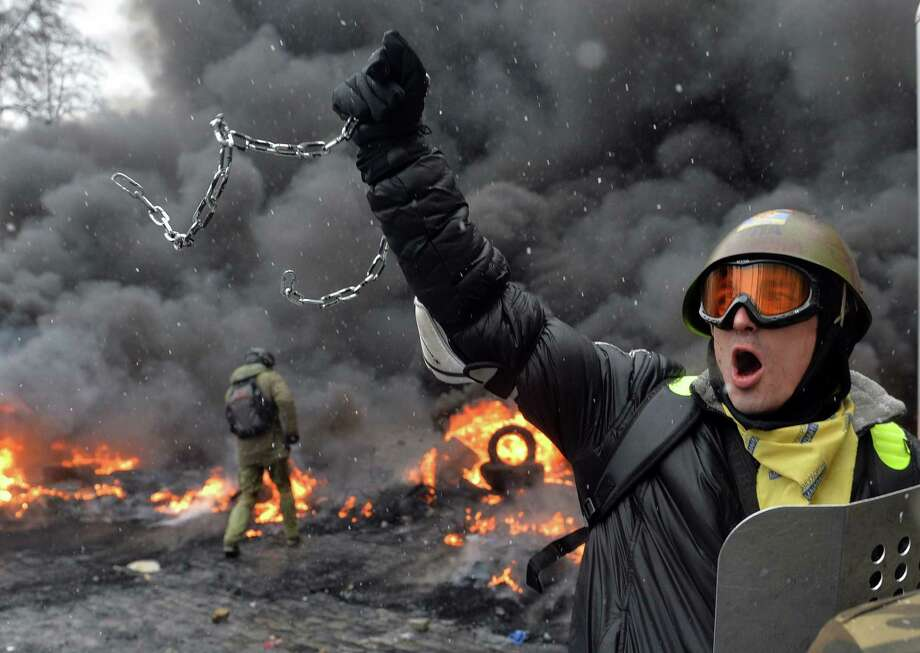 Protestors clash with police in the center of Kiev.  At least two activists were shot dead as Ukrainian police stormed protesters' barricades in Kiev, the first fatalities in two months of anti-government protests. Photo: Sergei Supinsky / AFP / Getty Images / AFP