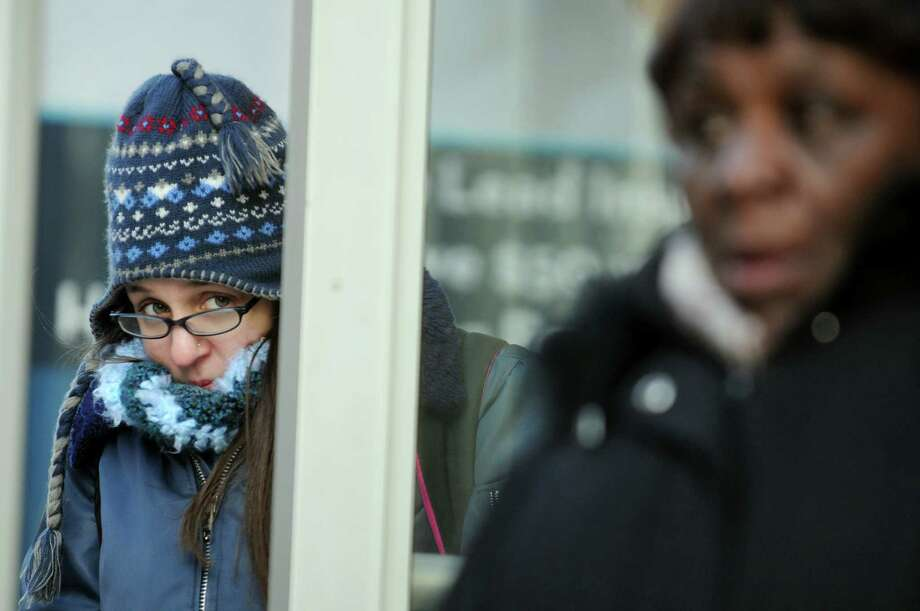 Emily Hudson of Troy, left, tries to stay warm as she waits for a bus on State Street on Wednesday, Jan. 22, 2014, in Albany, N.Y. (Cindy Schultz / Times Union) Photo: Cindy Schultz / 00025459A