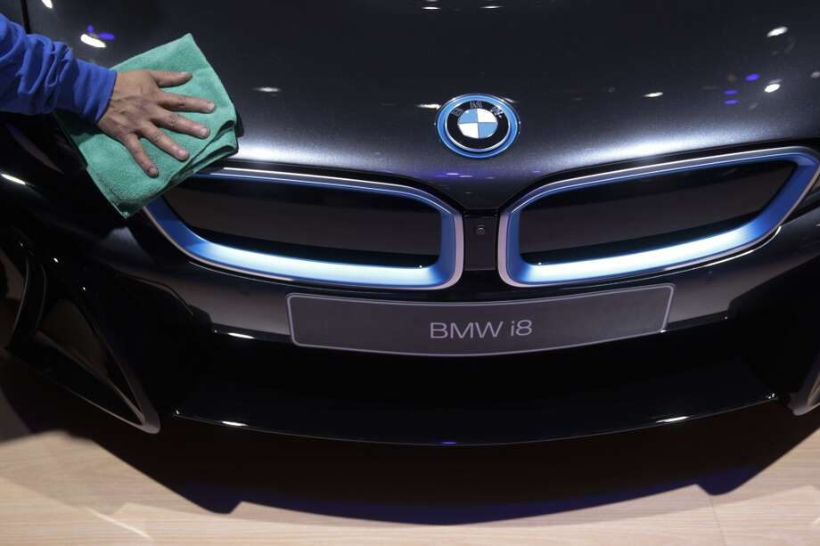 A worker cleans a Bayerische Motoren Werke AG (BMW) i8 electric sports vehicle during the 2014 North American International Auto Show (NAIAS) in Detroit, Michigan, U.S., on Monday, Jan. 13, 2014. Photo: Andrew Harrer, Bloomberg