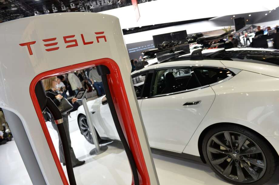 The Tesla P85+ all electric car and its charging station are displayed at the North American International Auto Show on January 14, 2014 in Detroit. Photo: STAN HONDA, AFP/Getty Images