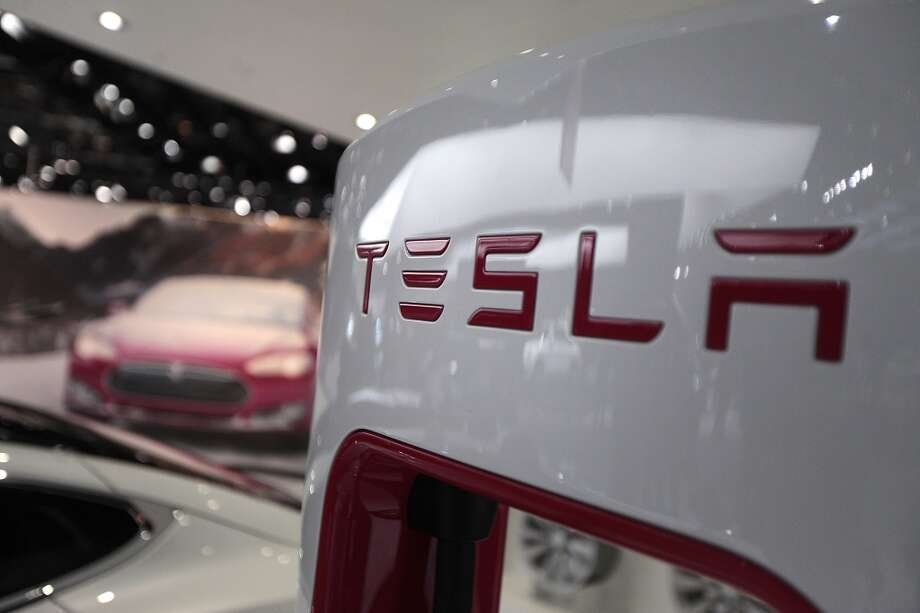The Tesla Motors Inc. logo is seen on a charging station at the company's booth during the 2014 North American International Auto Show (NAIAS) in Detroit, Michigan, U.S., on Tuesday, Jan. 14, 2014. Tesla Motors Inc., the maker of high-end electric cars, gained the most in six weeks after the carmaker said it delivered 6,900 Model S sedans in the fourth quarter, pushing full-year sales beyond a company target. Photo: Andrew Harrer, Bloomberg