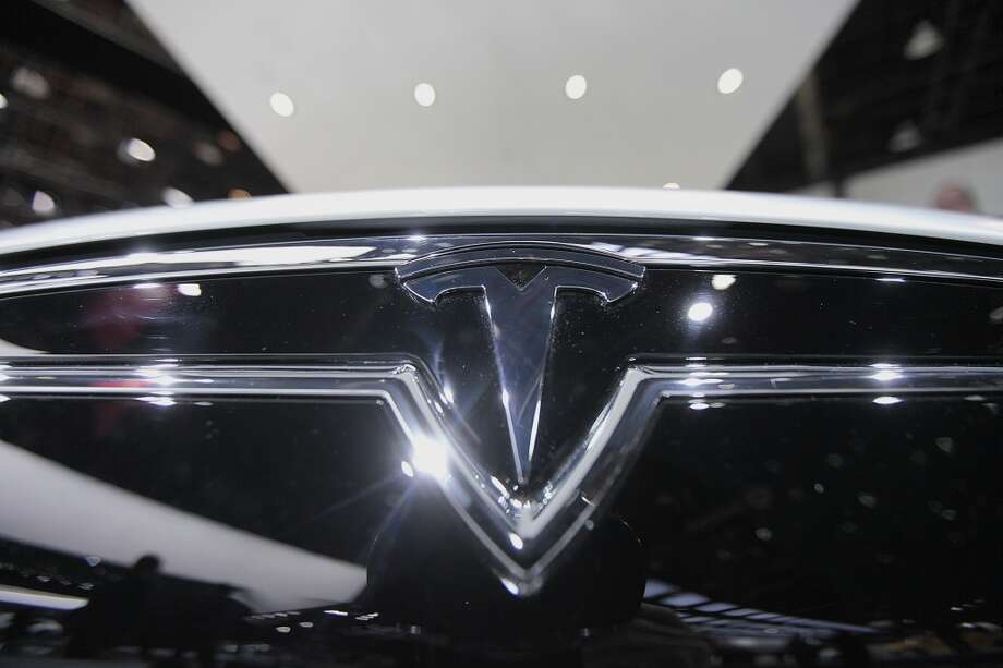 The Tesla Motors Inc. logo is seen on a Model S sedan at the company's booth during the 2014 North American International Auto Show (NAIAS) in Detroit, Michigan, U.S., on Tuesday, Jan. 14, 2014. Tesla Motors Inc., the maker of high-end electric cars, gained the most in six weeks after the carmaker said it delivered 6,900 Model S sedans in the fourth quarter, pushing full-year sales beyond a company target. Photo: Andrew Harrer, Bloomberg