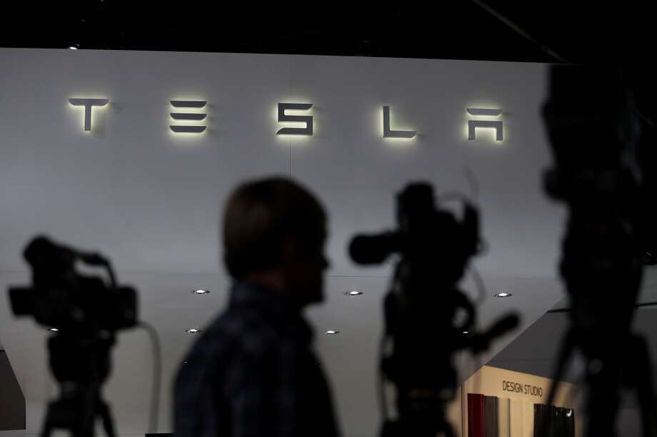 The Tesla Motors Inc. logo is seen as the silhouettes of members of the media arrive at the company's booth during the 2014 North American International Auto Show (NAIAS) in Detroit, Michigan, U.S., on Tuesday, Jan. 14, 2014. Tesla Motors Inc., the maker of high-end electric cars, gained the most in six weeks after the carmaker said it delivered 6,900 Model S sedans in the fourth quarter, pushing full-year sales beyond a company target. Photo: Andrew Harrer, Bloomberg