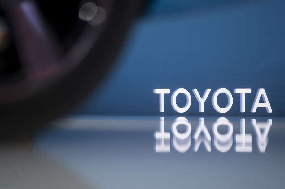 The Toyota Motor Corp. logo is seen past a FCV Concept hydrogen electric vehicle on display at the Washington Auto Show in Washington, D.C., U.S., on Wednesday, Jan. 22, 2014. Photo: Andrew Harrer, Bloomberg