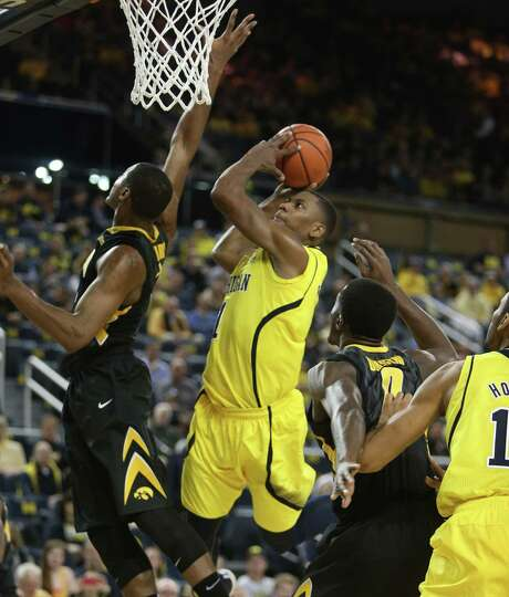 Michigan's Glenn Robinson III (right) drives against Iowa's Melsahn Basabe (left). Michigan travels to in-state rival Michigan State on Saturday in a game that pits the last two teams unbeaten in Big Ten play. Photo: Kirthmon F. Dozier / Detroit Free Press / Detroit Free Press