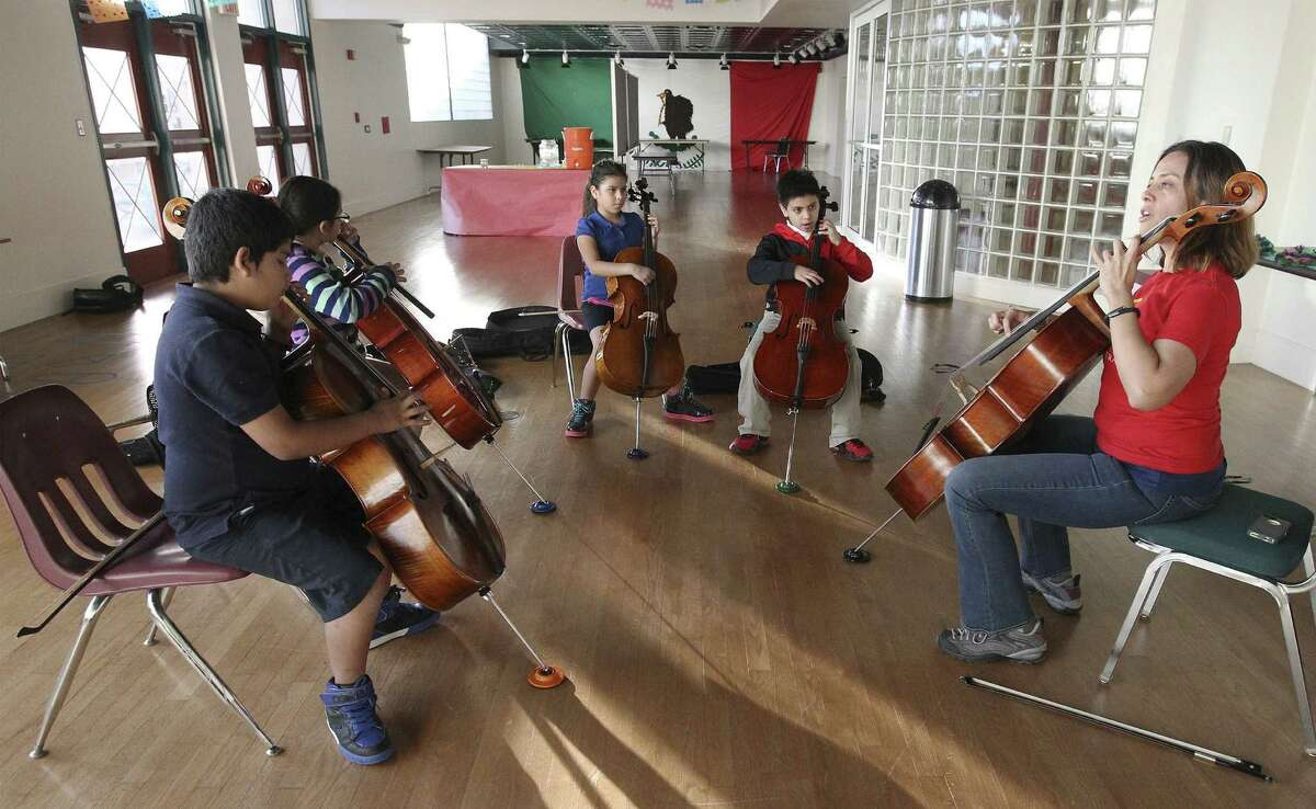 Aurelia Rocha, director of YOSA Mas, leads a group of children in learning to play the cello at the Edgewood ISD Fine Arts Academy.