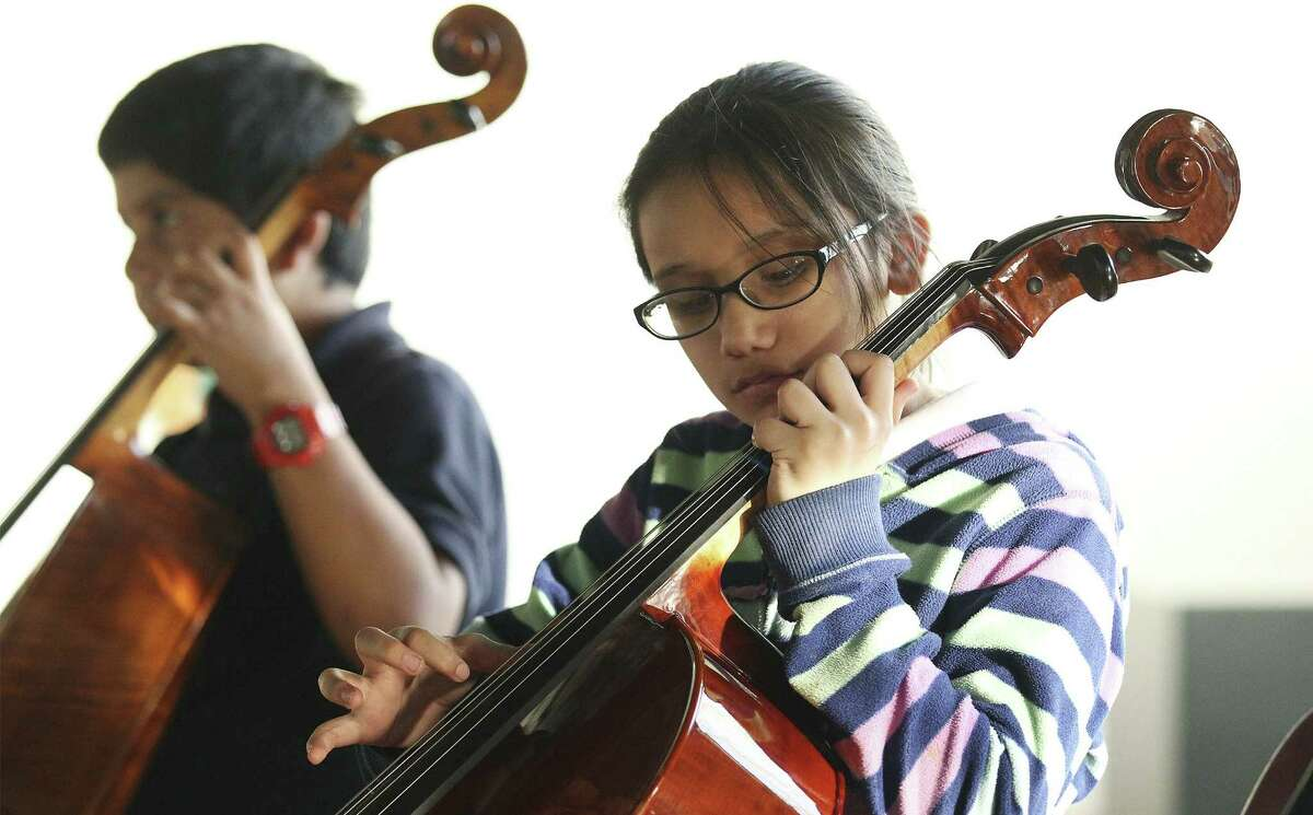 Alyssa Alvarez practices playing on her cello. The Edgewood district is bolstering music education with a new band hall and the Steinway piano.