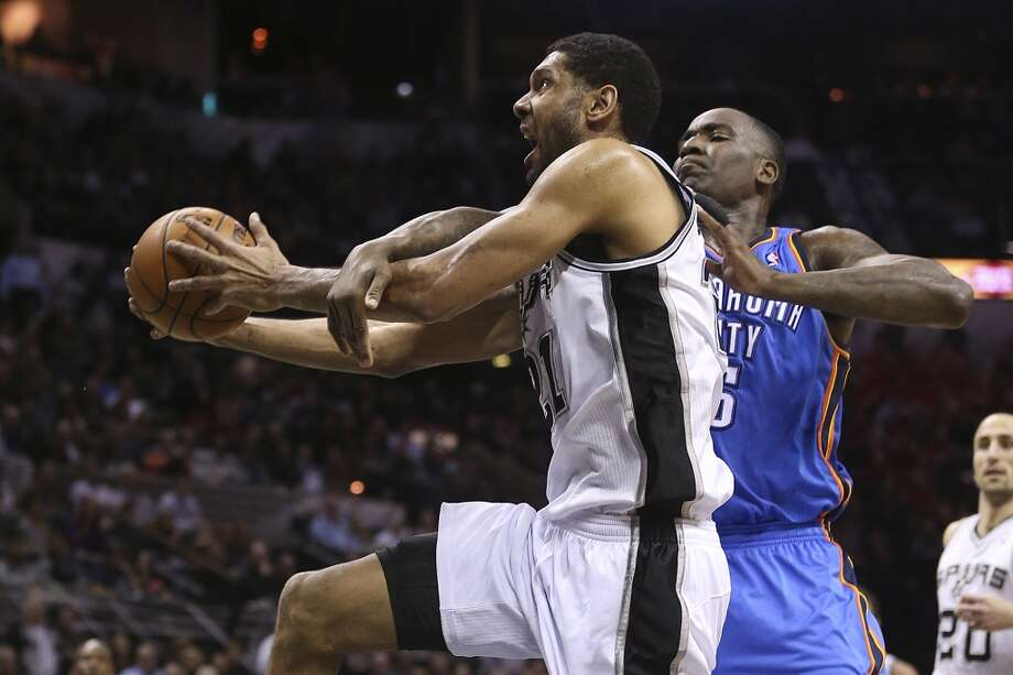 After stealing the ball, San Antonio Spurs' Tim Duncan is fouled by Oklahoma City Thunder's Kendrick Perkins during the first half at the AT&T Center, Wednesday, Jan. 22, 2014. Photo: San Antonio Express-News