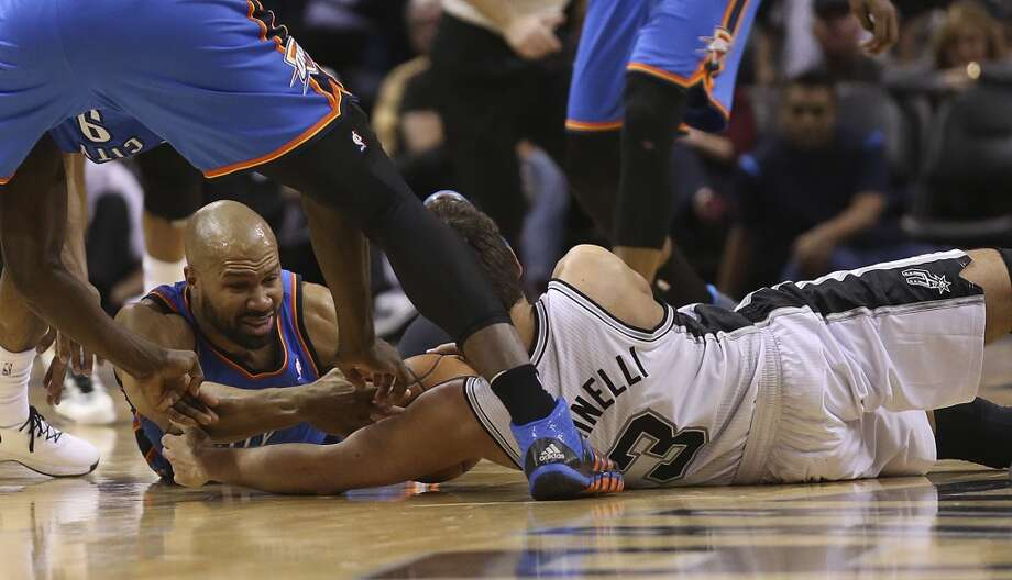 Okahoma City Thunder's Derek Fisher and San Antonio Spurs' Marco Belinelli scramble for a loose ball that turns into a scuffle during the second half at the AT&T Center, Wednesday, Jan. 22, 2014. The Thunder won 111-105. Photo: San Antonio Express-News
