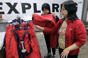 Seamstress Betty Beh (left) and supervisor Lydia Lam, inspect a line of outerwear designed for the U.S. Olympic freeskiing team at the North Face development center in San Leandro, Calif. on Wednesday, Jan. 15, 2014. The longtime Bay Area outdoor clothing and equipment company is outfitting the U.S. Olympic freeskiing team competing in Sochi, Russia. The limited edition clothing on the racks will be available to the public.