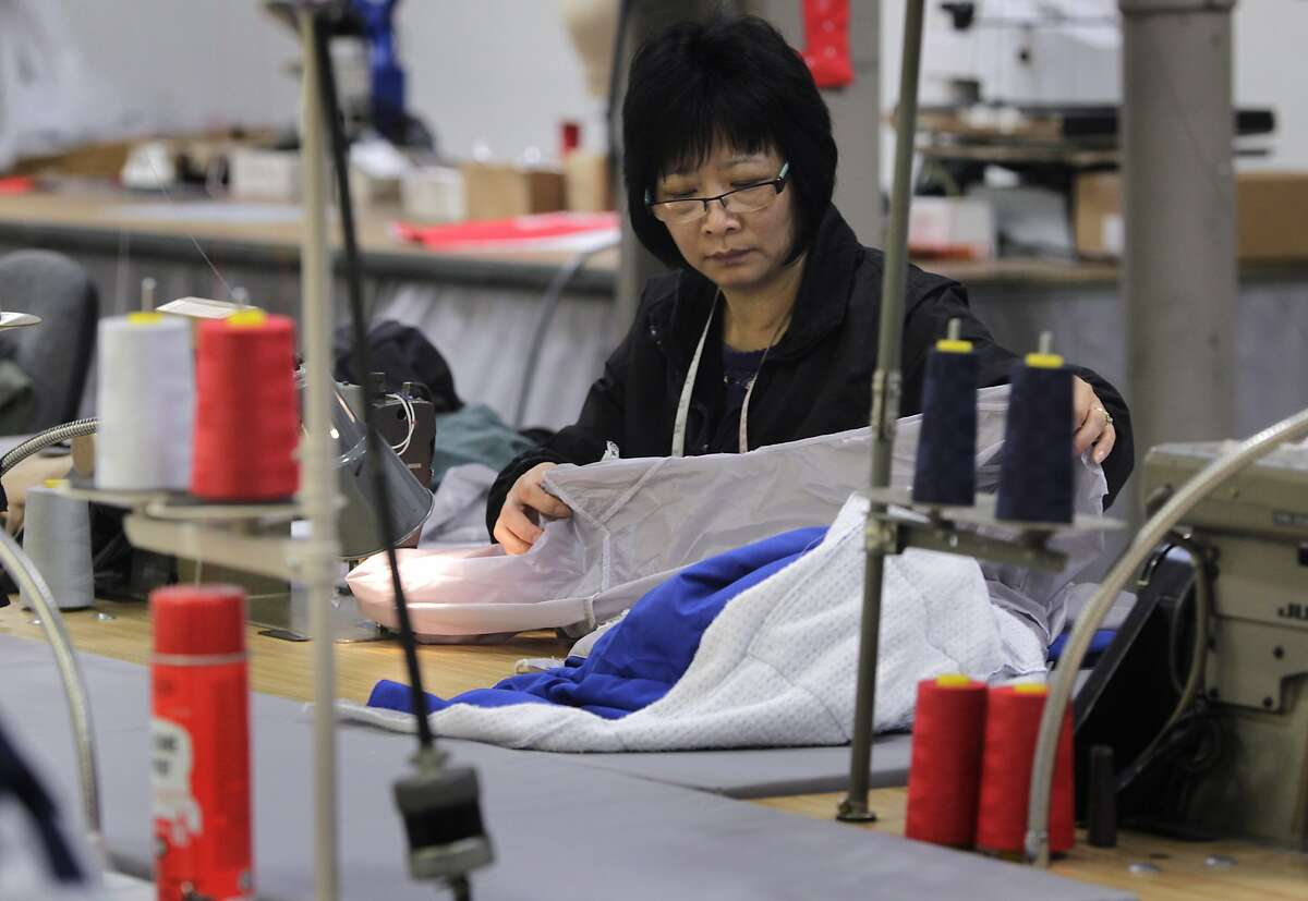 Aleyna Cao sews a garment at the North Face development center in San Leandro. North Face signed an eight-year deal with the U.S. freeskiing team in 2011.