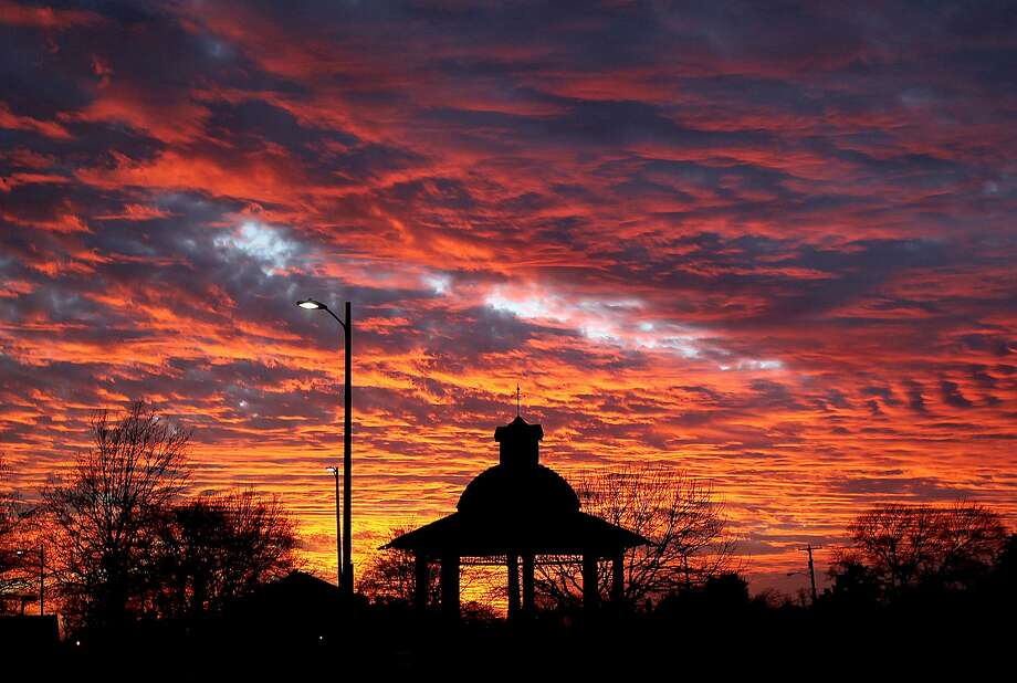 The sun reflects off of incoming clouds as it sets over the gazebo near downtown Waco, Texas. Photo: Jerry Larson, Associated Press