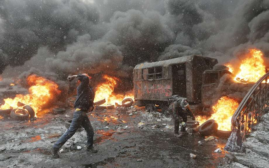 Kiev is a war zone: Protesters hurl rocks at police (off camera) as the snow falls on burning tires in central Kiev. Photo: Efrem Lukatsky, Associated Press