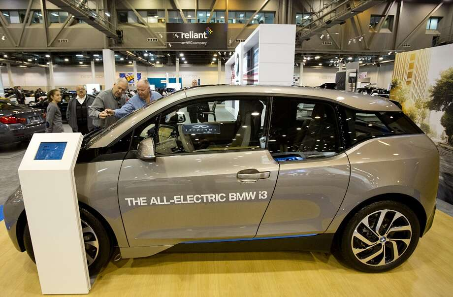 Jim Houck, left, and Robert Brickley of Porter take a look at the BMW-IE at the Houston Auto show at Reliant Center. The car will get 130 miles with a full electric charge and is listed for $43,000. Photo: Thomas B. Shea, Houston Chroncile