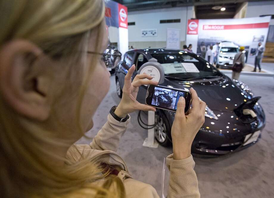 Rachel Prochaska, of Houston, takes a picture of the 2014 Nissan LEAF . The car lists for $28,800 and will travel 115 miles with a full electrical charge. Photo: Thomas B. Shea, Houston Chroncile