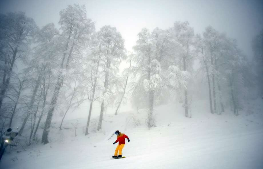 A snowboarder  takes a run on December 22, 2012 at the Rosa Khutor Mountain Resort in Krasnaya Polyana outside the Russian Black Sea resort of Sochi. Photo: MIKHAIL MORDASOV, AFP/Getty Images