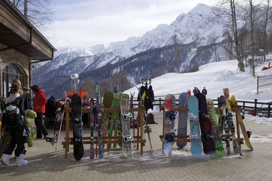 In this Wednesday, Feb. 6, 2013, file photo, snowboarders and skiers rest after competitions, in Rosa Khutor, some 60 km east of the Black Sea resort of Sochi, Russia. For visitors to the Winter Olympics, Sochi may feel like a landscape from a dream _ familiar and strange at once. Palm trees evoke a tropical seaside resort, but the Black Sea itself is seriously cold; turn away from the palms and the jagged, snow-covered peaks of the Caucasus Mountains rise nearby. Photo: Ivan Sekretarev, Associated Press