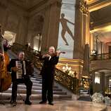 Members of the group Starlite Strings play for the guests of San Francisco Ballet's Opening Night Gala at City Hall in San Francisco, Calif., on Wednesday, January 22, 2014.  The decor, which was designed by  J. Riccardo Benavides, featured videos of dancers on the wall.
