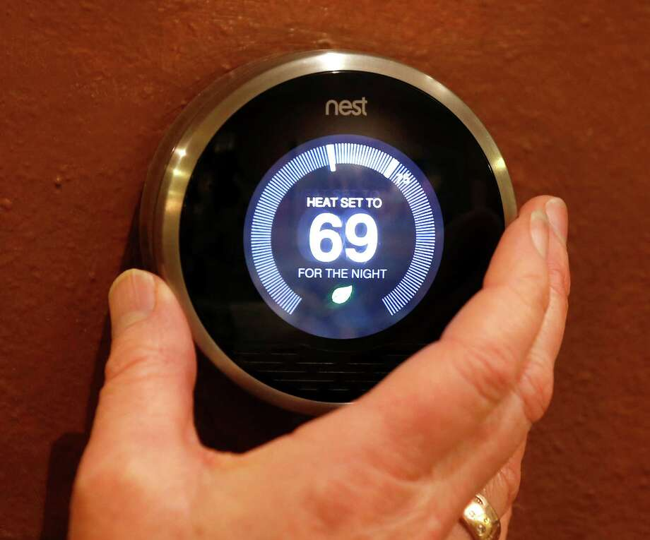 Smart thermostats, such as this model by the home-automation company Nest, can cut heating and cooling bills by raising or lowering temperatures automatically. Photo: George Frey, Getty Images / 2014 Getty Images