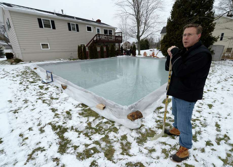 Home owner Paul Fahy stands with his home-built ice rink in the rear of his residence Monday morning Jan. 20, 2014 in Colonie, N.Y.       (Skip Dickstein / Times Union) Photo: SKIP DICKSTEIN / 0025423A