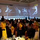 Guests of the San Francisco Ballet's Opening Night Gala sit down to enjoy their dinner at City Hall in San Francisco, Calif., on Wednesday, January 22, 2014.  The decor, which was designed by  J. Riccardo Benavides, featured videos of dancers projected on the walls.
