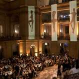 Guests of the San Francisco Ballet's Opening Night Gala sit down to enjoy their dinner at City Hall in San Francisco, Calif., on Wednesday, January 22, 2014.  The decor, which was designed by  J. Riccardo Benavides, featured videos of dancers projected on fabric hanging from the ceiling.