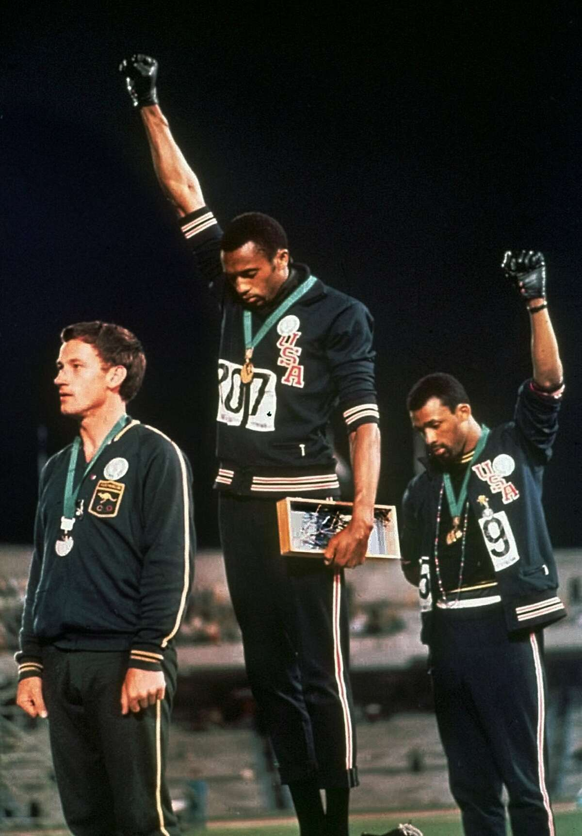 """Extending gloved hands skyward, United States athletes Tommie Smith, center, and John Carlos, right, stare downward during the playing of the """"Star-Spangled Banner"""" after Smith received the gold and Carlos the bronze for the 200 meter run at the Summer Olympic Games in Mexico City in this Oct. 16, 1968 file photo. Australia's silver medalist Peter Norman is at left."""