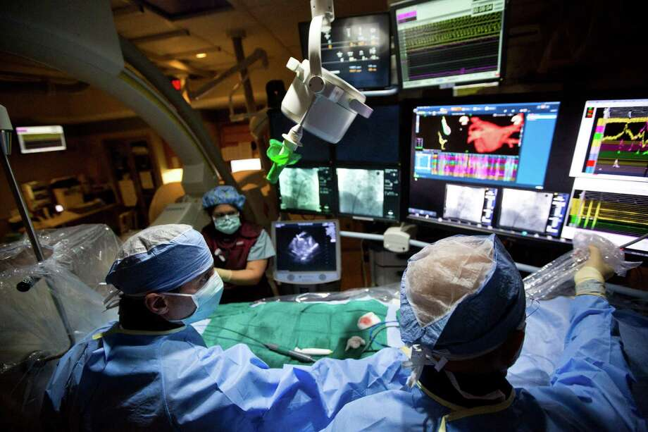 Dr. Abdi Rasekh, right, and Dr. Mehdi Razavi use a new 3-D atrial fibrillation mapping system at Texas Heart Institute to find the source of an abnormal heart rhythm in one of their patients. Photo: Marie D. De Jesus, Staff / © 2014 Houston Chronicle