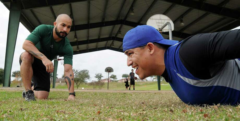 Trainer Andre Trinidad, left, puts Freddy Castillo through stretching and strength-training drills as part of a full-body workout program. Photo: Dave Rossman, Freelance / © 2013 Dave Rossman