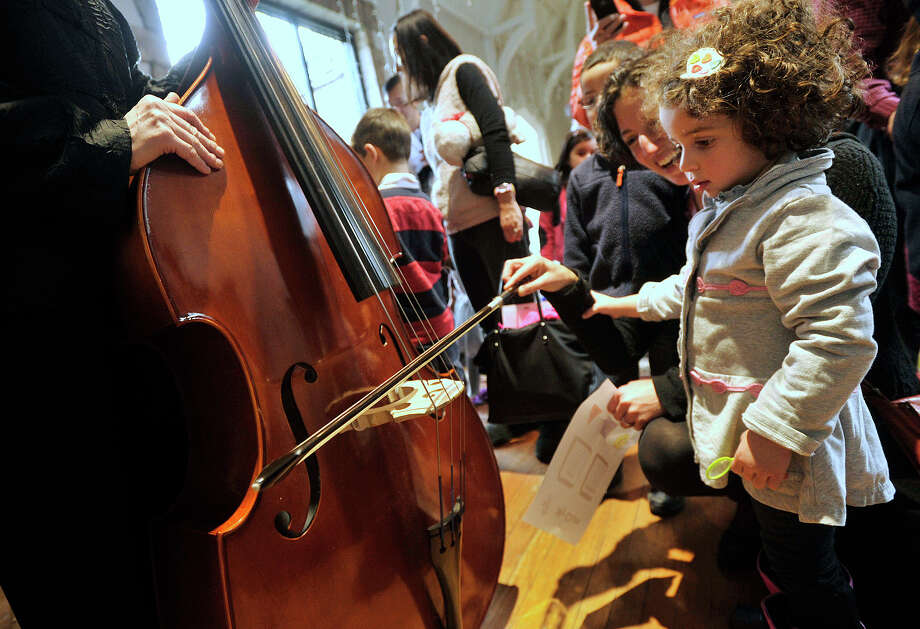 Alexandra Weiner gets a quick lesson on how to play the bass from Judith Sugarman, left, with a little help from Alexandra's mother, Lindsay, during the Exploring the Orchestra series with musicians with the Stamford Symphony at the Stamford Museum & Nature Center in Stamford, Conn., on Sunday, Jan. 12, 2014. Sunday's presentation focused on The Case of the Suspicious Strings. On Feb. 2, the series with continue with The Case of the Worried Woodwinds and on March 9, is The Case of the Brilliant Brass. Photo: Jason Rearick / Stamford Advocate