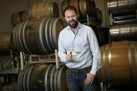 Graham Tatomer, 35, pictured in front of barrels of his Vandenberg Riesling 2011 wine Jan. 22, 2014 at the winery Brewer Clifton in Lompoc, Calif. Tatomer started his own label in 2008 but has been in the industry since he was 16 years old.