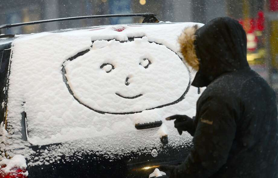 Put on a happy face: A New Yorker tries to cheer up a car after a winter storm dumped a foot of snow in the Big Apple. Photo: Emmanuel Dunand, AFP/Getty Images