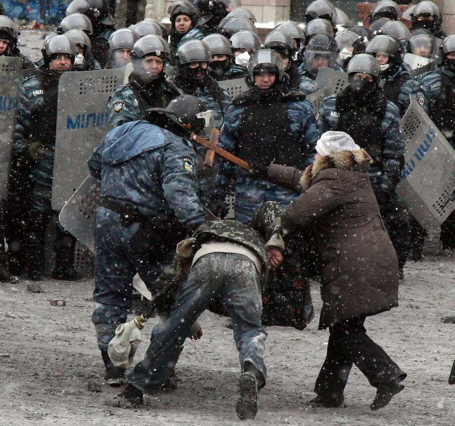 Cross with the police: A woman whacks a riot police officer with a cross as he hauls away a protester during clashes in Kiev. At least 