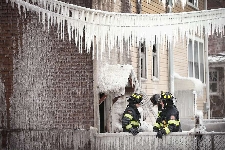 Busy morning: Firefighters take a break after braving single-digit temperatures to battle an apartment fire in Cicero, Ill. The fire department was fighting another multi-alarm blaze simultaneously in Cicero. Photo: Scott Olson, Getty Images