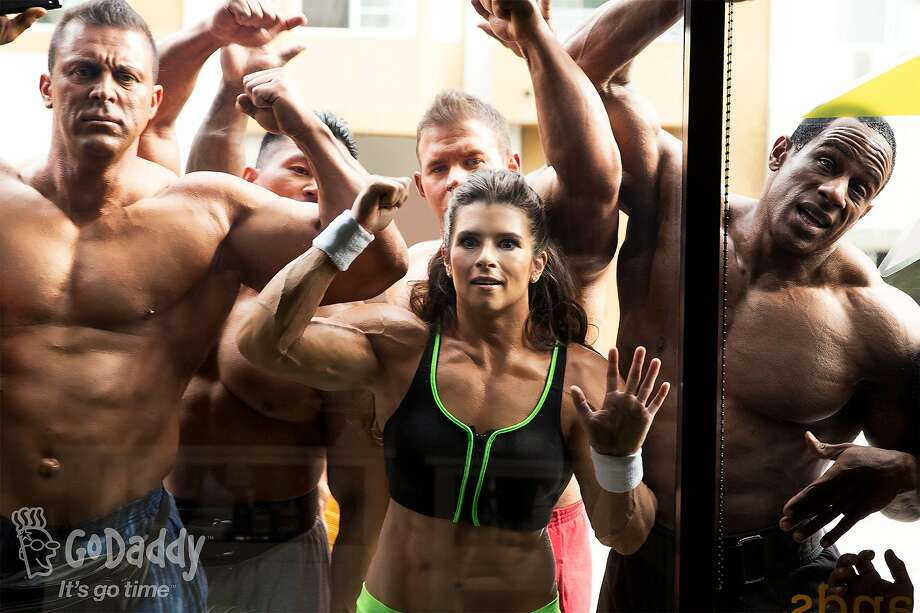 Muscled car driver: Judging from this handout image shot on location in Long Beach, Calif., NASCAR driver Danica Patrick has obviously been working out for her annual Super Bowl commercial for GoDaddy.com. Expect to see it in the second half. Photo: GoDaddy.com, Associated Press