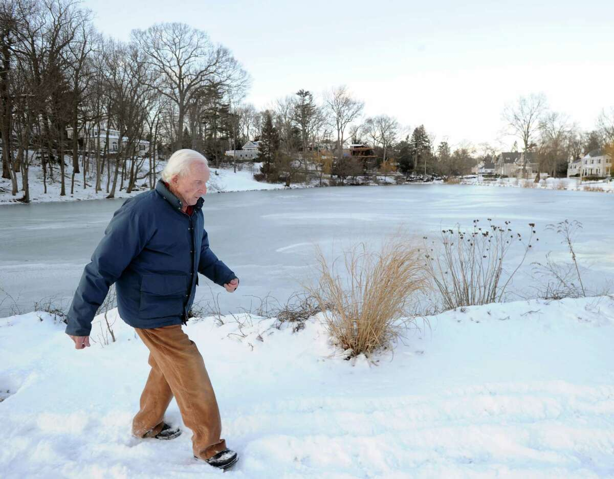 """Paul Palmer walks by the pond in front of his Willowmere Circle home in the Riverside section of Greenwich, Thursday, Jan. 23, 2014. Palmer was instrumental in helping to aid in the rescue of two kids who had fallen through the ice on the pond by calling for emergency help. Palmer said both kids were rescued and are in good condition. Palmer said """"this time of year I keep an eye out on the pond. Seems like every year someone falls through."""""""