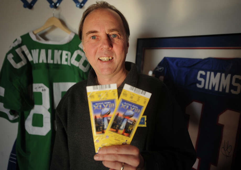 Sales Manager Mike Quinton holds a pair of Super Bowl tickets, with a face value of $800 a piece, at TicketPro.com at 150 Connecticut Avenue in Norwalk, Conn. on Thursday, January 23, 2014. Photo: Brian A. Pounds / Connecticut Post