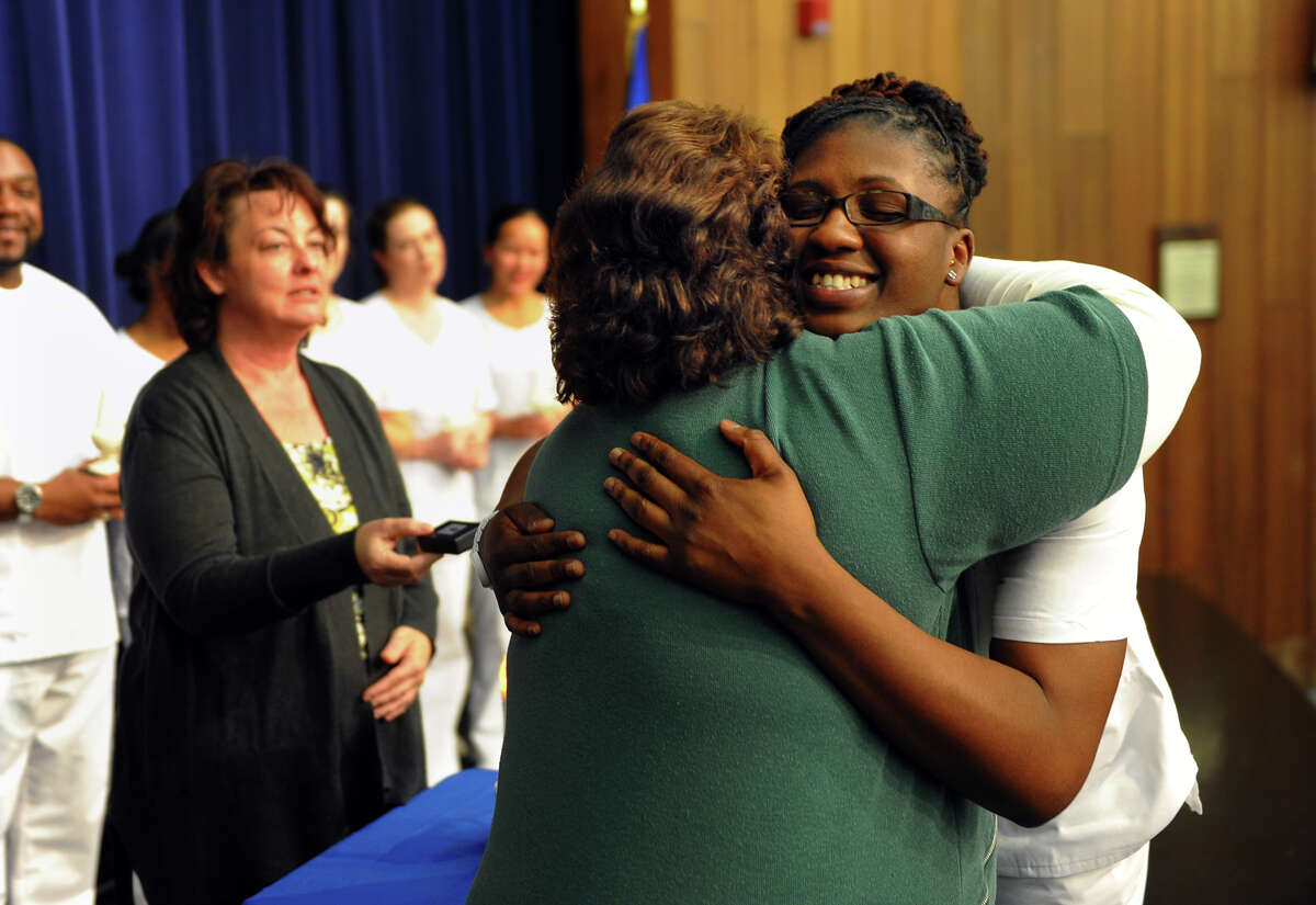 Karriane Sterling hugs Kathleen Bhatti MSN RN, after receiving her pin during a Pinning and Candle Lighting Ceremony for the Stratford campus of Porter and Chester Institute's first ever graduating class of nurses at Bunnell High School in Stratford, Conn. on Thursday January 23, 2014.
